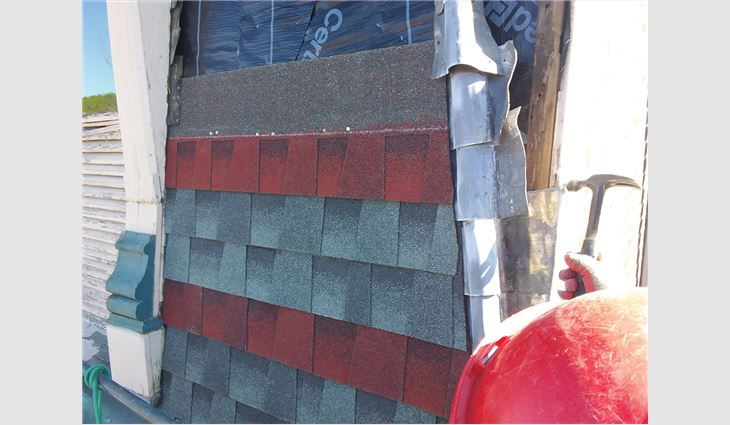 Workers followed a design pattern on drawings to install new asphalt shingles.
