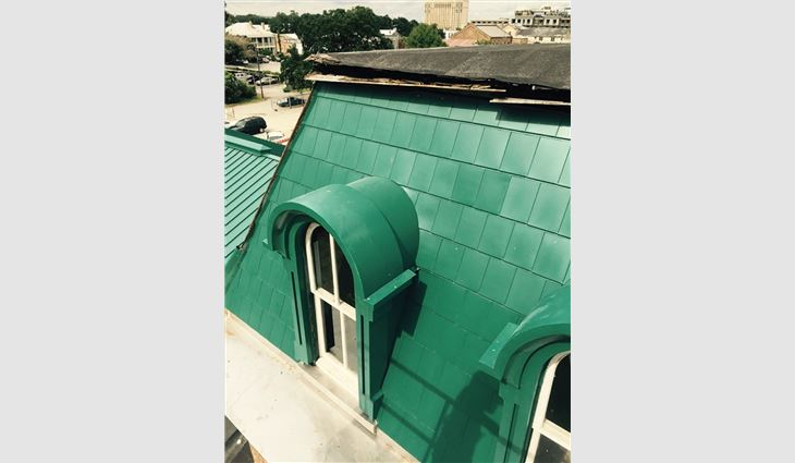 Custom-fabricated metal dormer covers and shingles were painted green