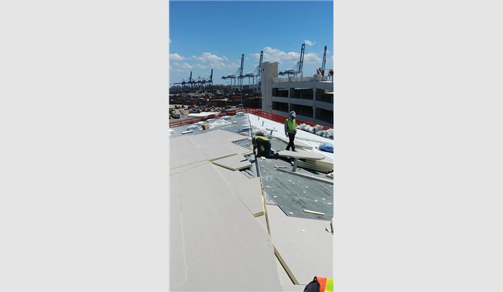 The crew applied two layers of polyisocyanurate insulation in a staggered pattern to the roof decks on the steep-slope areas.