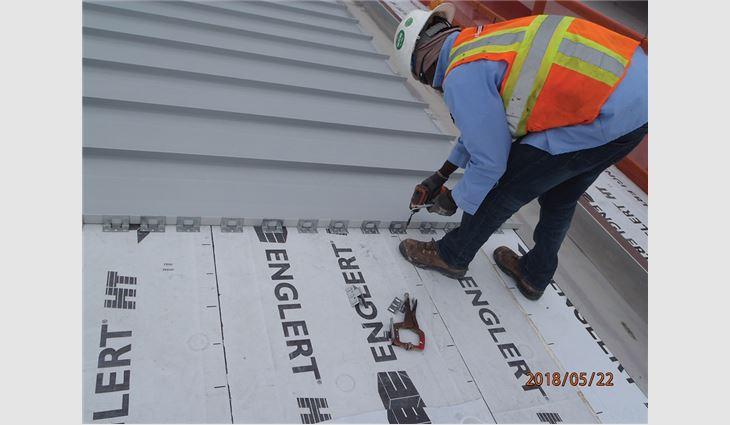 A worker installs metal panels