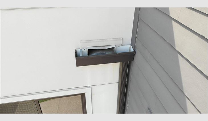 The contractor chose to install a through-wall scupper into a small gutter with no face plate.