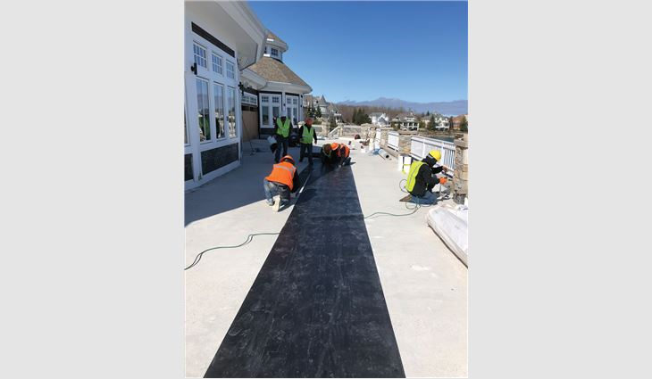 Workers loosely laid a specially designed drainage mat before installing the paver system.