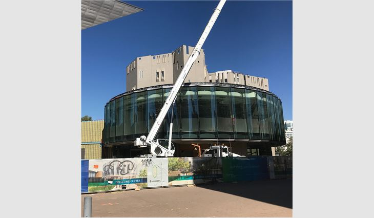 On the one-of-a-kind curved-glass curtain wall system, workers installed custom-fabricated 20-ounce scalloped-shaped flat-seam panels and custom-fabricated triangle-shaped snowguards.