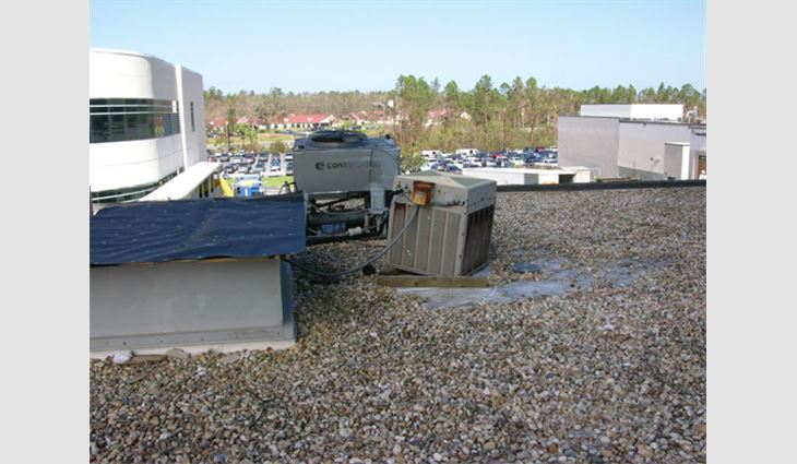Photo 2: Water entered this building where the equipment blew off the curb. Note that an adjacent condenser shifted off its sleepers. Even in areas with low wind speeds, sleepers typically offer inadequate wind resistance. To resist ASCE 7 loads, equipment typically will need to be anchored to flashed curbs or equipment stands.