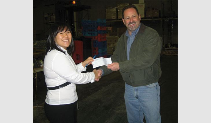 Charlie McCurry, S&K Roofing, Siding and Windows' sales director and food drive coordinator, gives a $2,000 check to Rebecca Pon, Maryland Food Bank's special events and food drive coordinator.