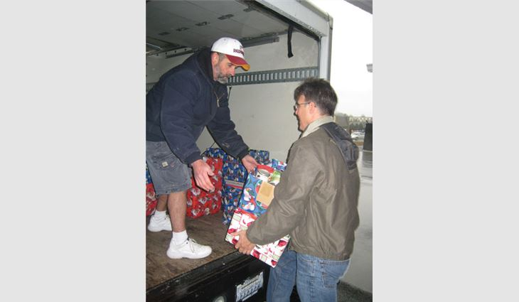 Don Katzenberger, owner of S&K Roofing, Siding and Windows, and Ray Smallwood, the company's operations manager, load a truck with donated items.