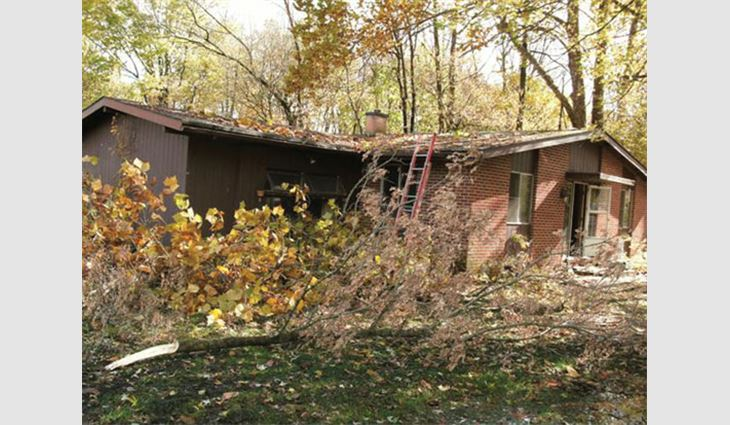 The exterior of Betty's home before Bone Dry Roofing performed renovations