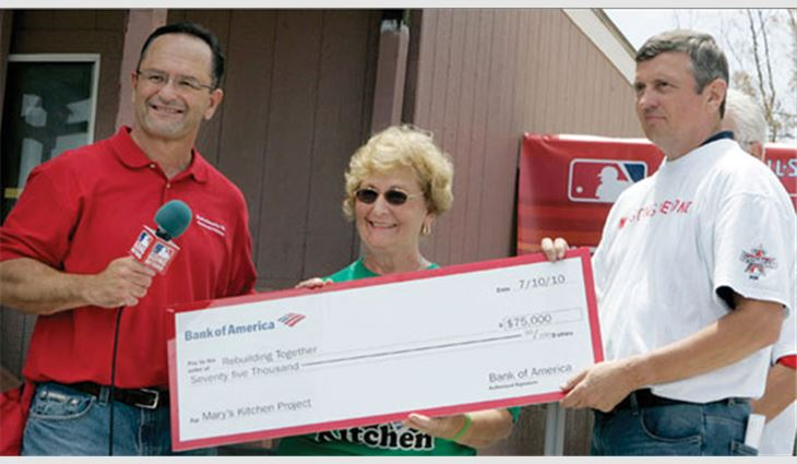 Allen Staff (left), senior vice president and regional executive for Bank of America, and NRCA Executive Vice President and Rebuilding Together's Chairman of the Board Bill Good present a $75,000 check to Gloria Suess of Mary's Kitchen, which was rehabilitated by Rebuilding Together, Bank of America and Major League Baseball.