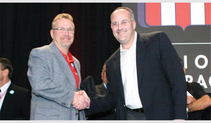 Denton shakes hands with Josh Kelly, vice president and general manager of OMG Roofing Products, Agawam, Mass., and a member of the MVP Task Force, after receiving the Best of the Best Award.