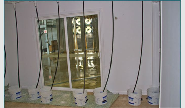 Photo 3: Water collection drains and buckets in the duplex