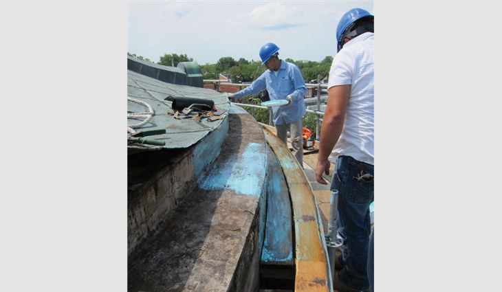 Workers restore the existing flat-seam roof and built-in gutter.