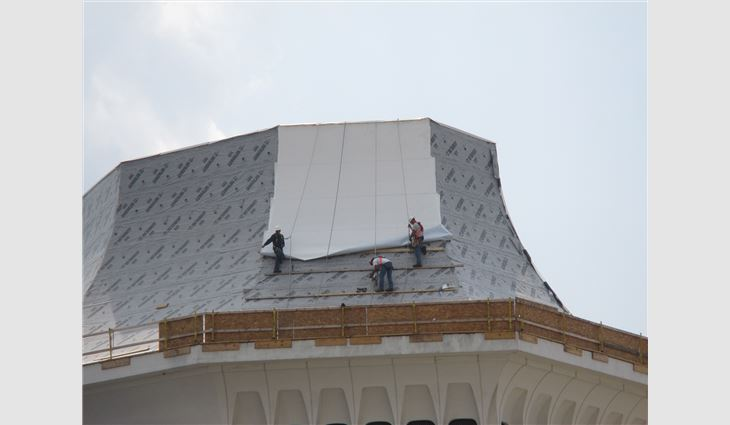 Workers apply the TPO membrane