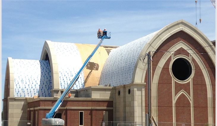 Workers installed new nail-base insulation and underlayment on the church's curved roof