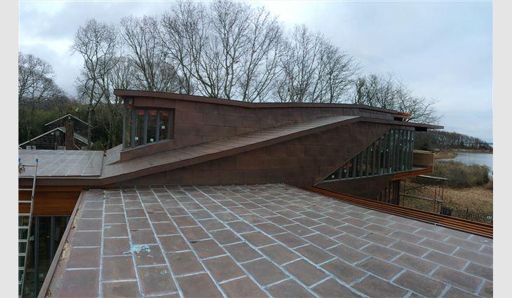 TRM Enterprises craftsmen soldered copper sheet panels on low-slope roof areas.