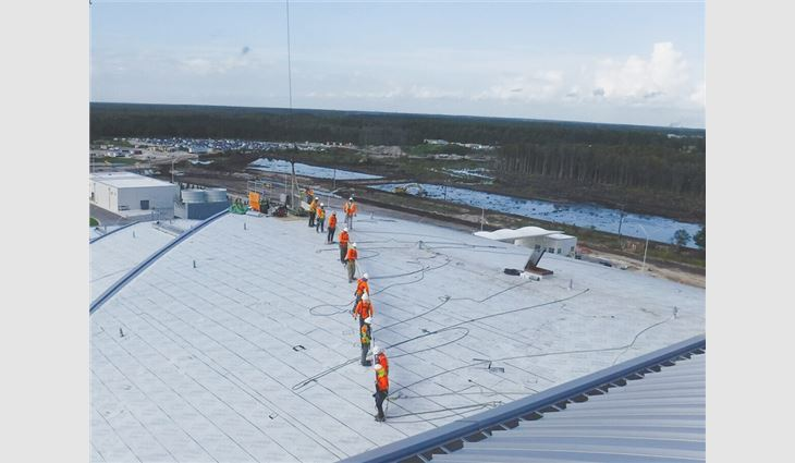 Workers move a roof panel across the rooftop.
