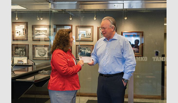 David Humphreys, president and CEO of TAMKO Building Products, presents a $100,000 check to Stacy Burks, executive director of the American Red Cross of Southern Missouri, for disaster relief efforts.