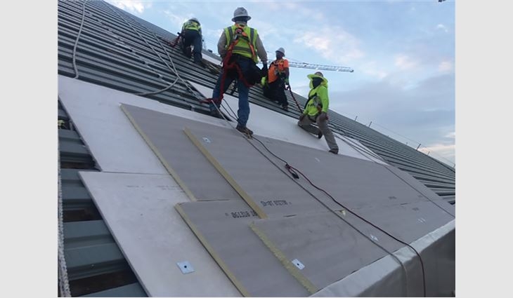 Workers install new standing-seam Galvalume® panels.